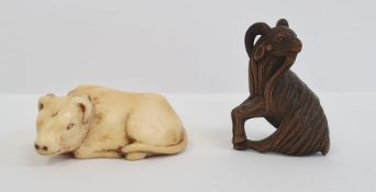 Japanese carved ivory netsukein the form of a seated bullock, 5cm long and a Japanese carved wood