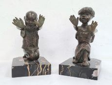 Pair of bronze and marble figural bookendseach in the form of a kneeling figure with outstretched
