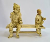 Late 19th century Japanese carved ivory group of two figures seated on bench (each figure with