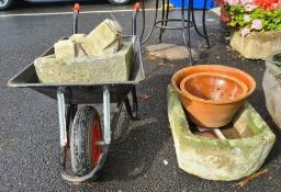 Gardeners wheelbarrow containing D-end stone trough and four stone cornice pieces, another D-end