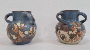 Pair H Brannam Barum glazed terracotta three-handled vases, each foliate decorated on a blue ground,