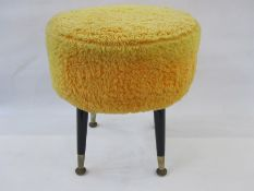 Mid-20th century circular padded stoolon ebonised tapering supports with yellow covering, 42cm