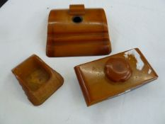 An Art Deco Carvacraft amber resin inkwell, blotter and desk tidy (3)