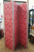 Three fold screen, covered in red damask, with red and gold braid detail