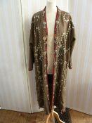 Full-length kaftan-style khaki twill coat, heavily embellished with Indian-style decoration of metal