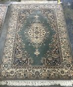 A Persian style wool rug: a royal Keshan rug wool, light green blue ground central foliate medallion