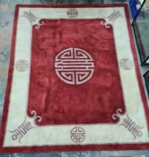 A Chinese wool rug, red ground with central symbol in purple, cream border with symbols and edging