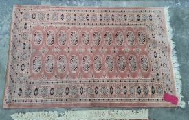 Persian style rug with pink ground, elephant's foot guls, blue and red border, 147cm x 95cm