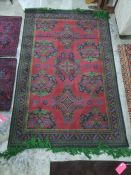Eastern, possibly Turkish, red ground rug with repeating motifs, in red, green, blue design and