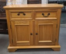 Modern oak cabinet, the rectangular top with canted corners, two drawers, two cupboard doors,