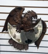 Early 20th century Black Forest mirrormodelled as a carved eagle holding a crescent-shaped bevelled