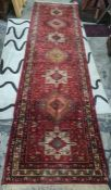 Persian style wool runner, red ground with lozenge and square medallions, floral borders, with one