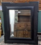 19th century ebonised wall mirror with wavy moulded border, central rectangular bevelled mirror