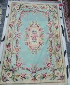 Rug with turquoise ground, the central medallion decorated with flowers, on a single marching