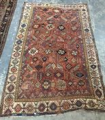 Red ground rug, possibly Persian, and possibly circa 1860, with allover hooked arabesques and