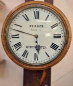 A 20th Century oak circular wall clock, Pearce York St, Westminster, Roman numeral enamel dial, 38cm