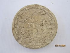 Archaeological find, a small carved stone roundel, the centre with Arabic script within a double