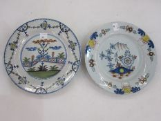 English delft plate, floral decorated and a delft plate decorated with zigzag fence in a garden,