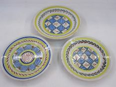 Three Delft plates, two with cross-hatch decoration in blue, red and green, with laurel to rim and