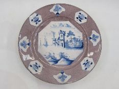 18th century delft plate with underglaze blue waterside decoration on a powder manganese ground,
