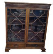 Early 20th century mahogany glazed bookcasehaving stiffleaf and beaded borders to the pediment,