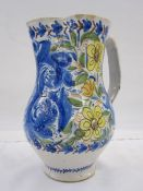 Italian faience jug decorated with scrolling flowers in a blue, green, yellow and orange palette,