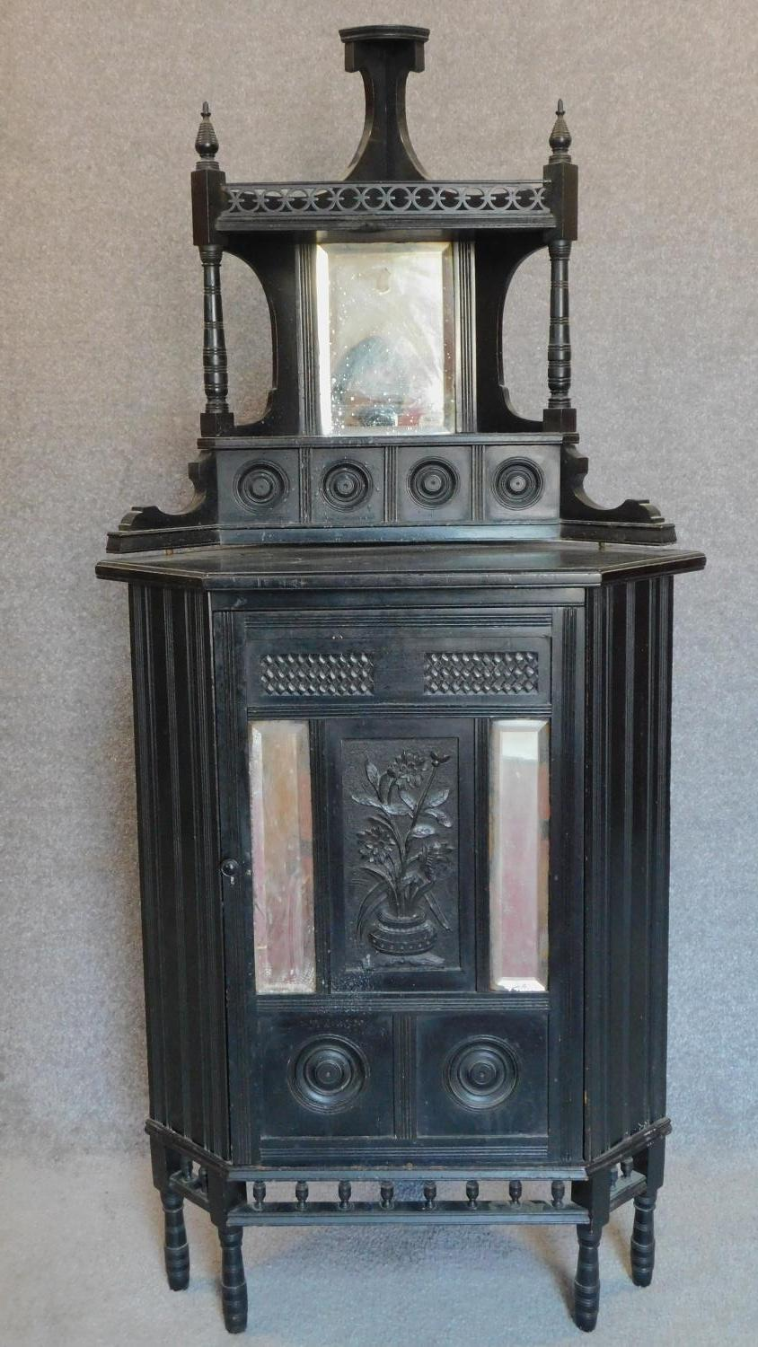 Lot 17 - A late 19th century ebonised corner cabinet with mirrored back and carved panels in the aesthetic