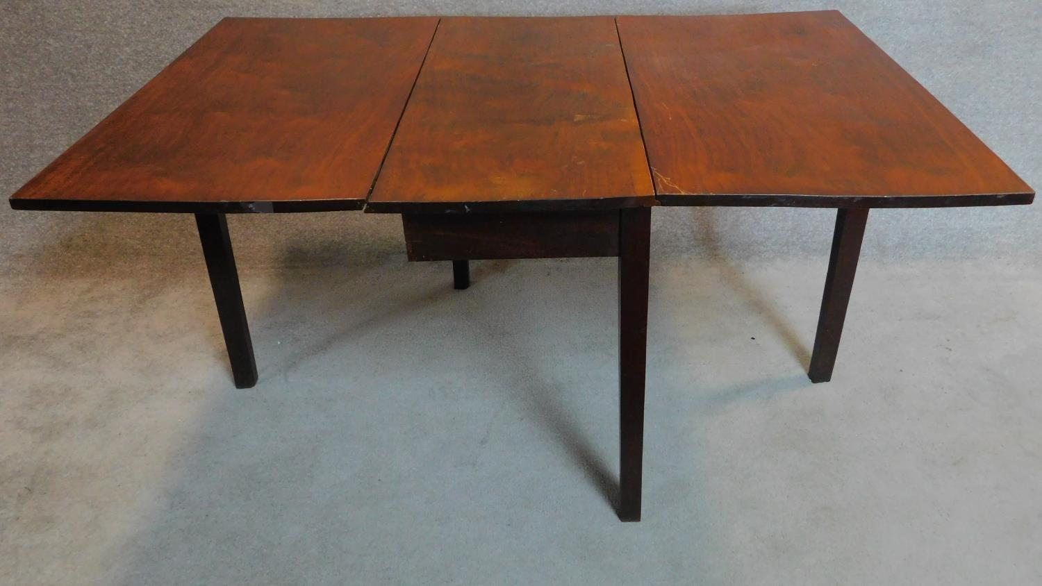 Lot 15 - A Georgian mahogany drop flap dining table on square section supports. 73x148x99cm