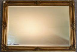 A gilt framed wall mirror with rectangular bevelled plate. 73cm x 100cm