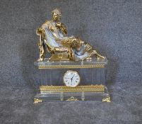 A large French Empire style mantel clock with gilt metal reclining figure above perspex case on gilt