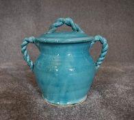 A Persian glazed ceramic blue pot with lid. H.20cm x W.18cm