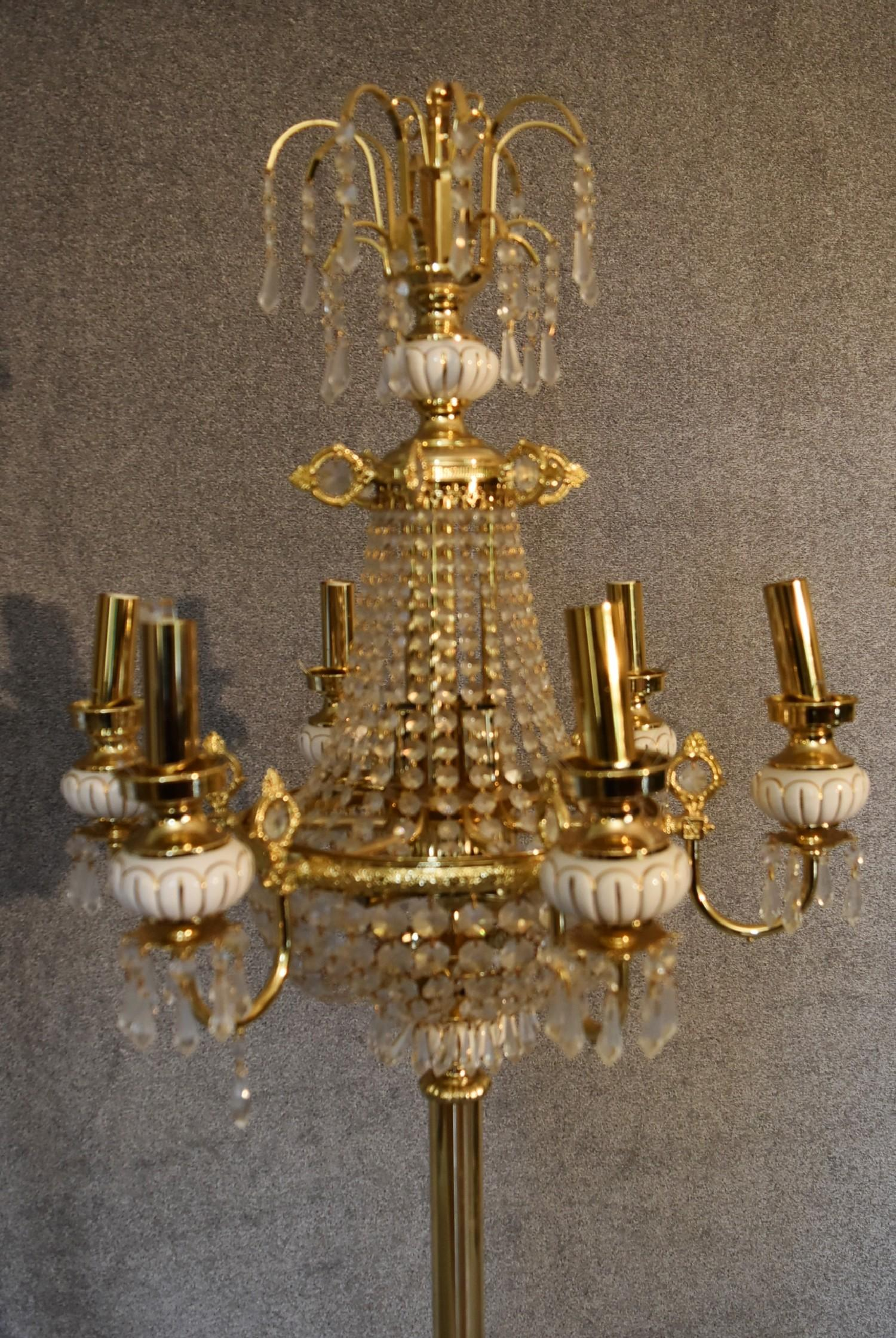 Lot 11 - A gilt metal and crystal floor standing six branch chandelier. 1.8m tall.