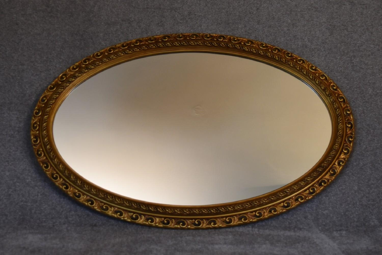 Lot 8 - A gilt framed oval wall mirror with gadrooned and floral edging. L.115cm x 75cm.