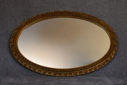 A gilt framed oval wall mirror with gadrooned and floral edging. L.115cm x 75cm.