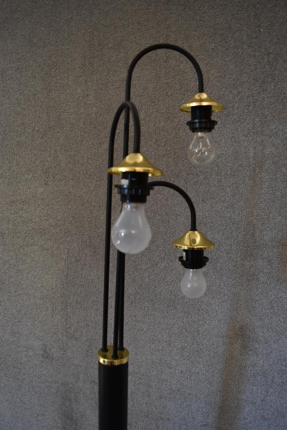 Lot 14 - A floor standing lamp with black base and three branches each with brass light fittings,