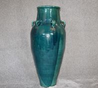 A large green drip glazed sharab wine vessel with six handles. H.94cm