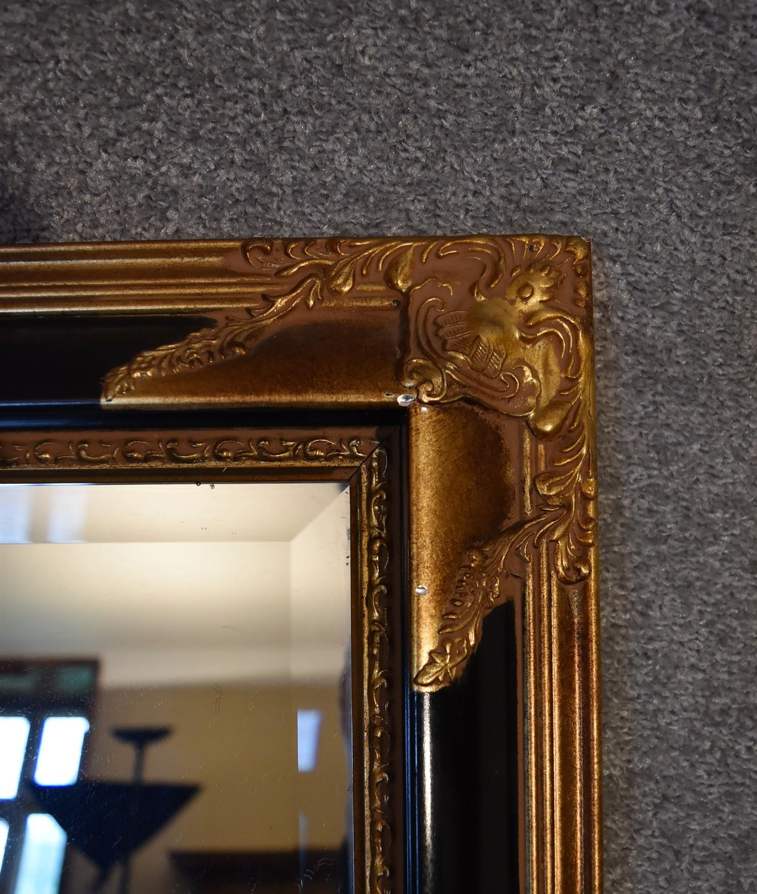 Lot 9 - A gilt and ebonised decorative wall mirror with bevelled plate. 1.2m x 90cm.