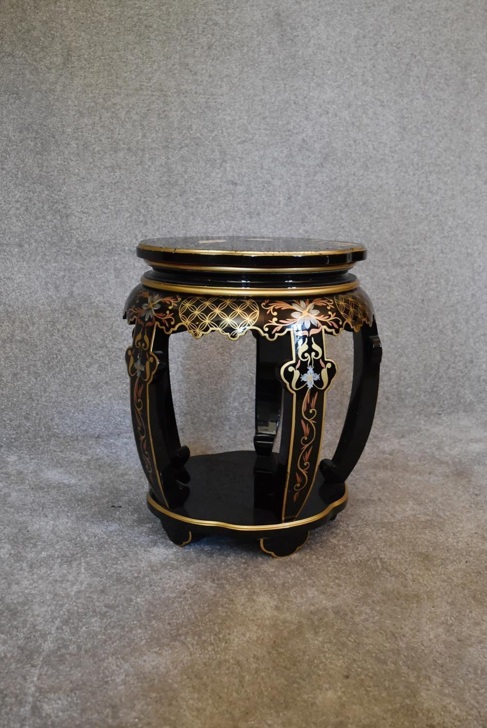 Lot 20 - A black lacquered and gilt decorated Chinese stool. 50cm tall x 35cm diameter.