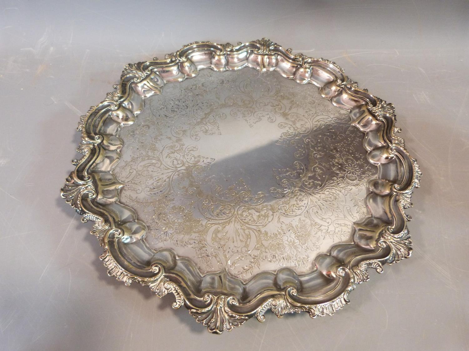 Lot 10 - A collection of silver plate including a four footed repousse design tray, toast rack, swing