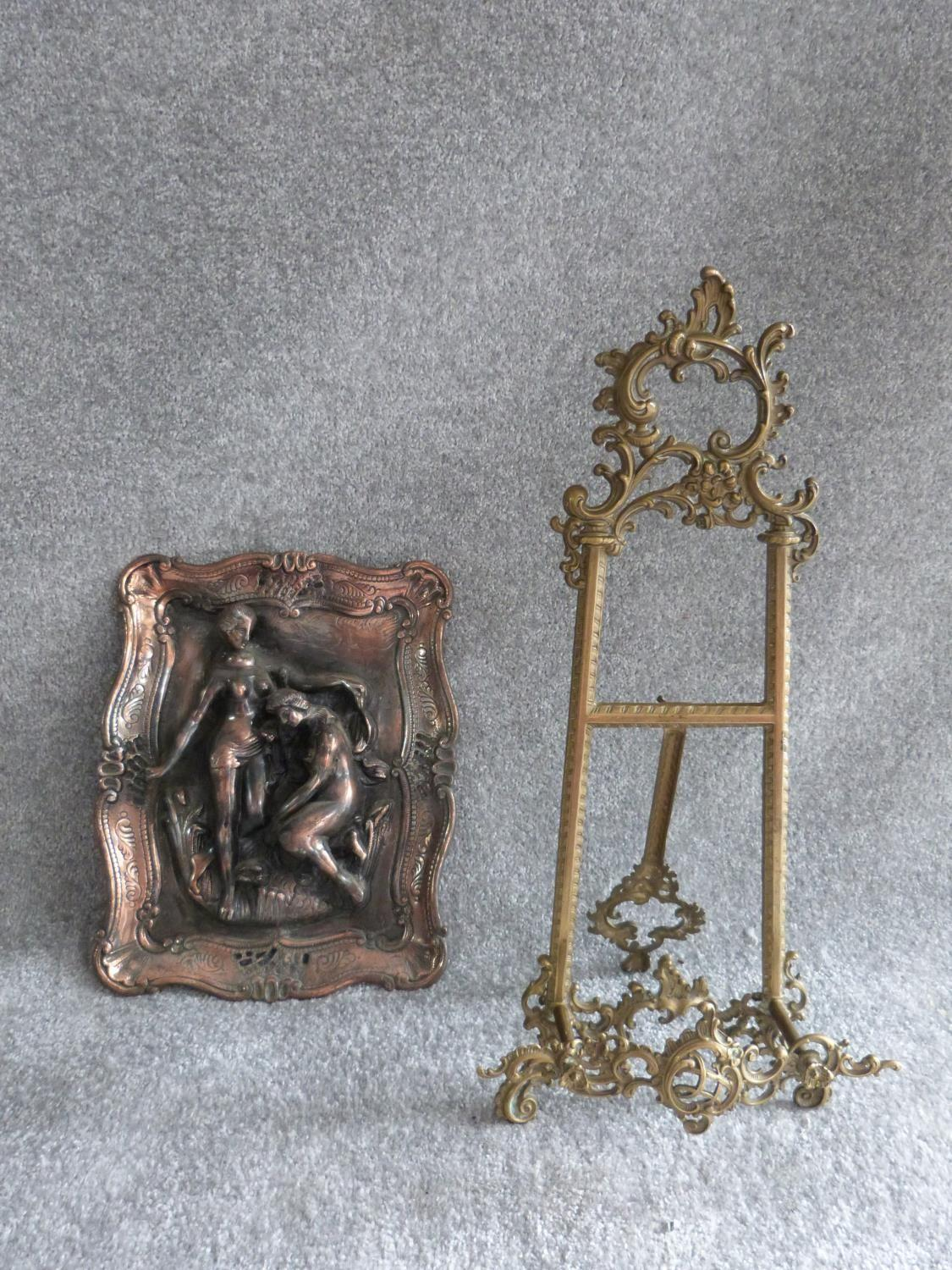 Lot 27 - A copper relief moulded wall plaque with male and female figures and a vintage brass openwork easel.