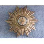 A vintage sunburst giltwood clock by Smiths Sectric. Label on side. H 40cm.