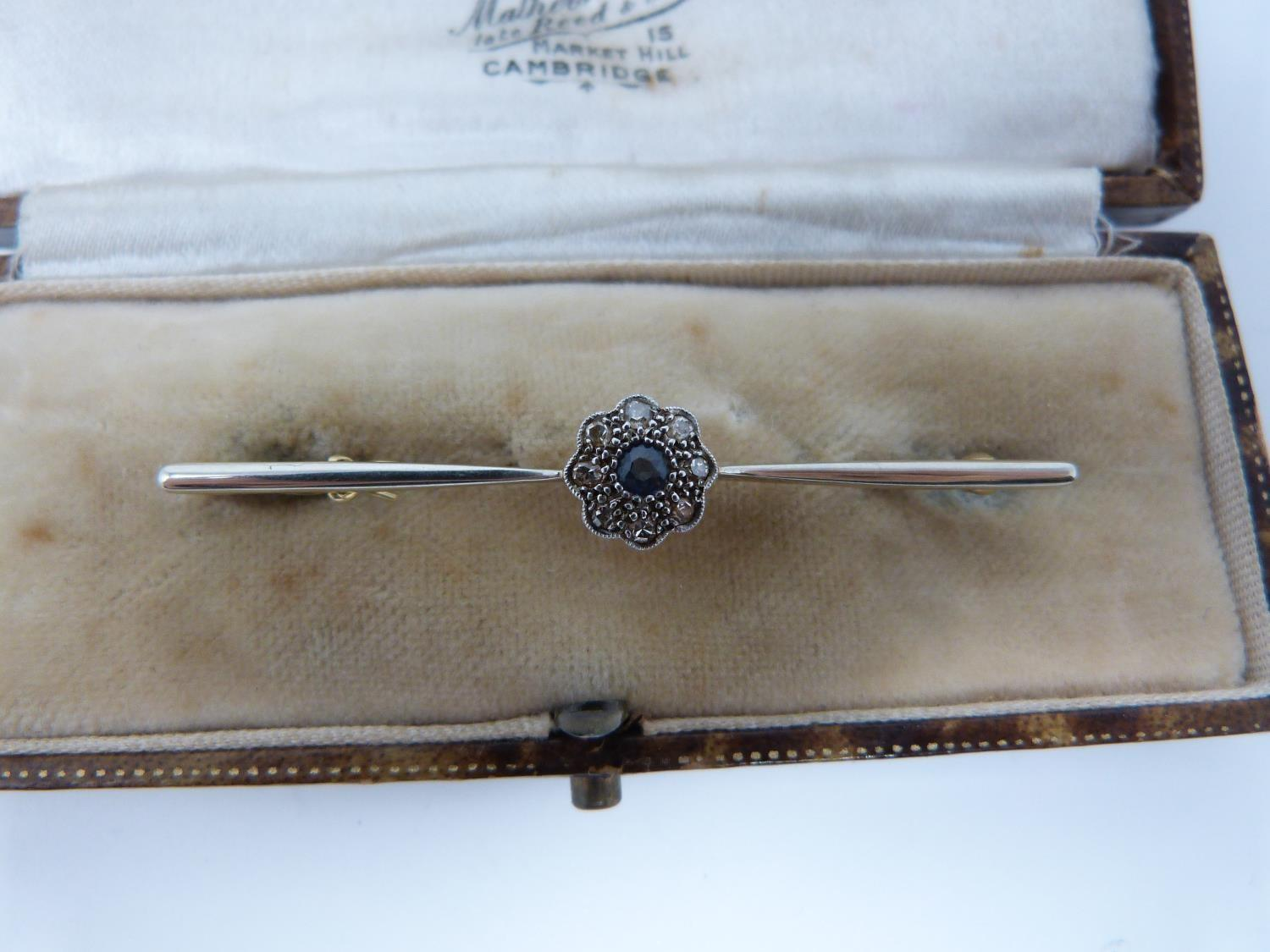 Lot 3 - A diamond and sapphire 15 carat gold bar brooch, set to centre with a round old cut sapphire with an