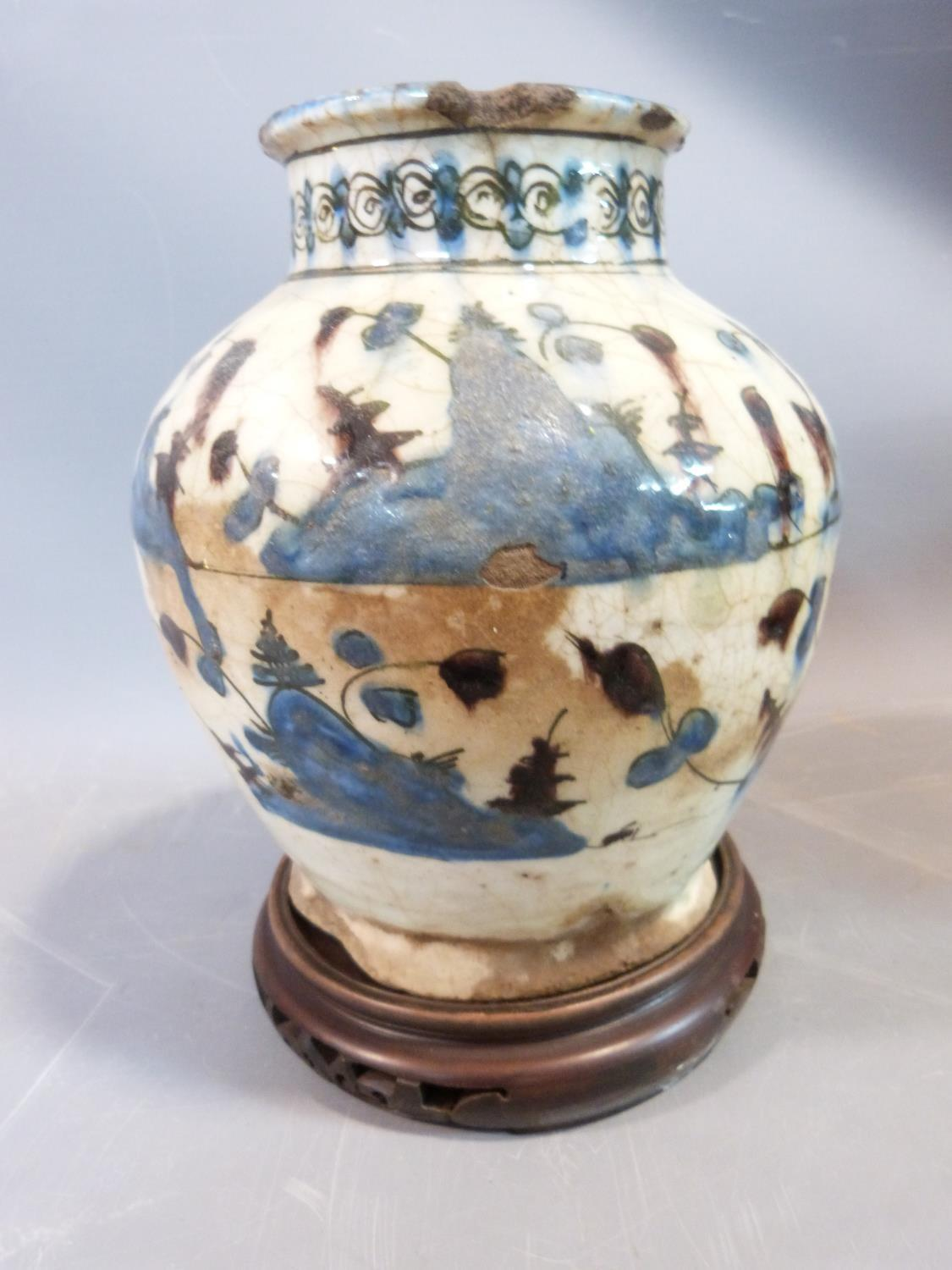 Lot 25 - A middle eastern ceramic glazed vase on carved wooden Chinese stand. H23cm.