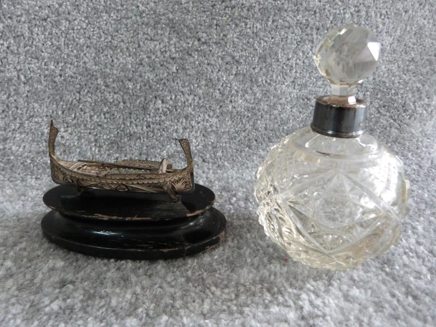 Lot 4 - A silver collared cut glass perfume bottle and a silver wire boat on wooden stand. Perfume bottle