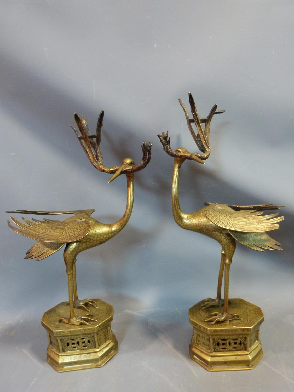 Lot 12 - A pair of 19th century brass Chinese herons holding bamboo shoot candlesticks, with engraved