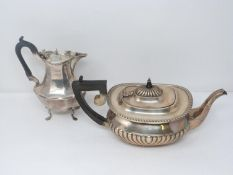 An antique silver coffee pot and tea pot. The Victorian Coffee pot has angular design, maker JH