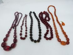 A collection of antique and vintage Amber and Amber plastic necklaces and an Amber pendant. Two