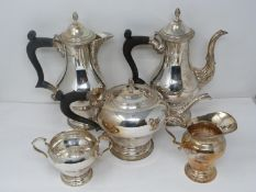 A five piece matching silver tea service. Includes a water jug, coffee pot, tea pot, sugar bowl