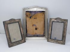 Three silver photo frames. One pair of silver repousse design photo frames with urn and floral
