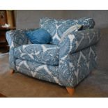 A large armchair with blue patterned fabric upholstery and two scatter cushions. H. 94 x 120 x 94cm